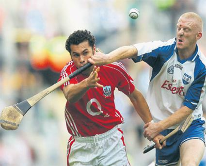 Cork's Seán Óg hAilpín gets a mouthful of ash from John Mullane as he handpasses the sliotar away during yesterday's All-Ireland SHC quarter-final in Croke Park.