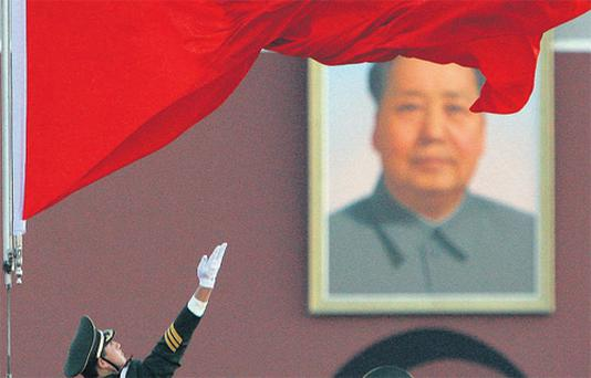 A soldier unfurls the Chinese national flag as it is raised in front of the giant portrait of Chairman Mao