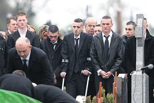 The body of 21-year-old Paul Quinn (pictured below) is lowered into a grave at St Patrick's Church cemetery, in his hometown of Cullyhanna, Co Armagh. Mr Quinn was brutally beaten to death by a gang of nine men