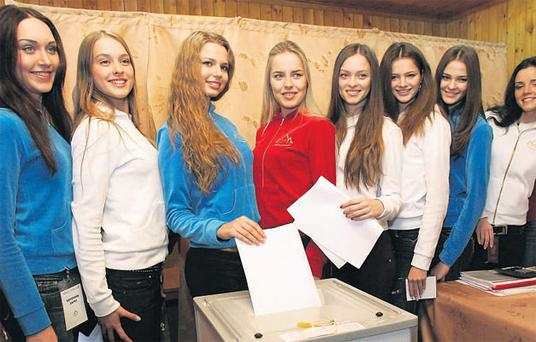Finalists of the Miss Russia 2007 beauty contest (above), decked out in the national colours, pose for cameras as they cast their votes in the village of Morozovka outside Moscow