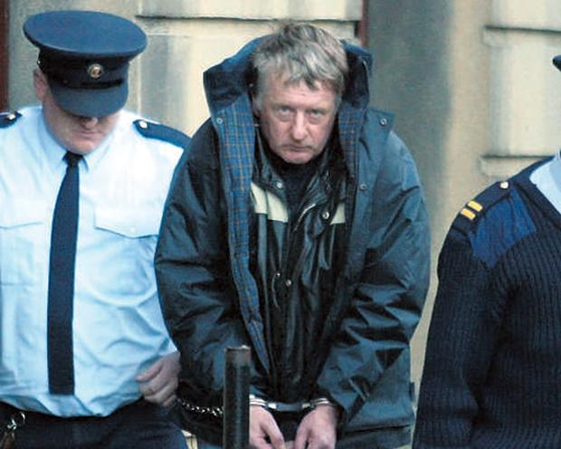 Martin Kinneavy is led away from the Central Criminal Court in Dublin yesterday after he was sentenced to life imprisonment for the murder of his partner
