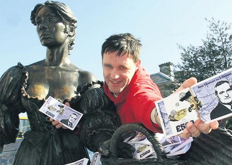 Artist Will St Leger handing out fake 'Bertie' banknotes at the Molly Malone statue in Dublin yesterday in protest at the Hill of Tara road development