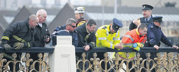 Rescue workers on Heuston Bridge near Dublin's Heuston Station (above) watch as colleagues help a man, who had jumped into the Liffey