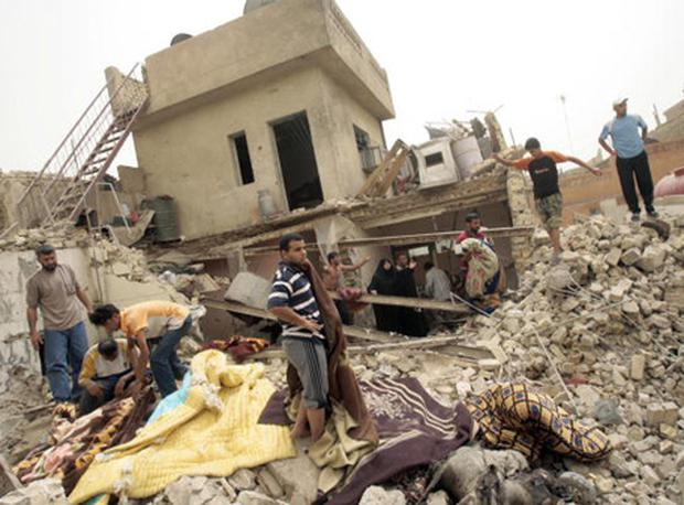 Iraqis cover with blankets the dead bodies of their neighbours and relatives in the ruins of a house hit in a US air strike in Baghdad Sadr City on April 29, 2008 (Photo by AHMAD AL-RUBAYE/AFP/Getty Images)