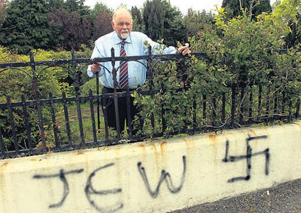 Herb Meyer shows the graffiti painted on the wall of his home in Tuam, Co Galway