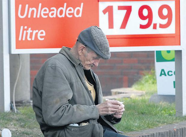 A man sits outside the One Oil filling station on Dublin's Usher Quay yesterday where motorists are being charged an astonishing €1.79.9 per litre for both petrol and diesel