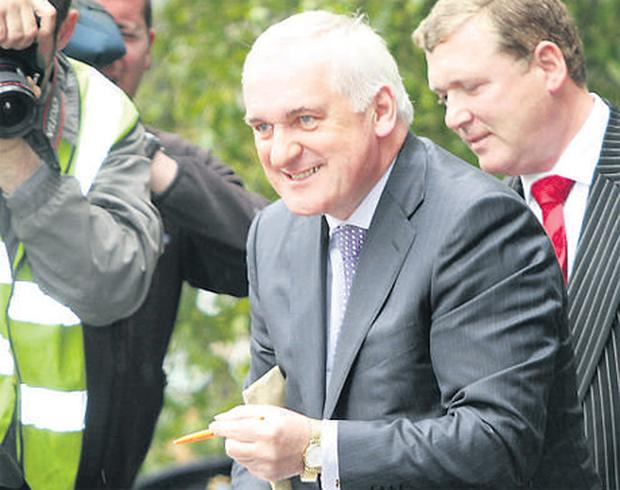 Former Taoiseach Bertie Ahern autographing a book entitled 'De Collection of Diaries of a Nortsoide Taoiseach' on his way into the Mahon Tribunal in Dublin Castle where he defended former secretary Grainne Carruth