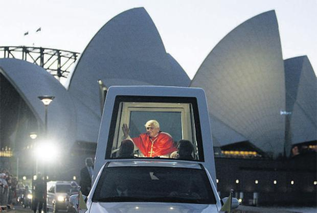 Pope Benedict waves to the crowds as he passes the Sydney Opera House in his Popemobile after addressing thousands of pilgrims for World Youth Day