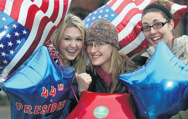 American students at Queens University Belfast, left to right, Jordan Junge, Jamie Ferguson and Anne Martz celebrate as Mr Obama is sworn in