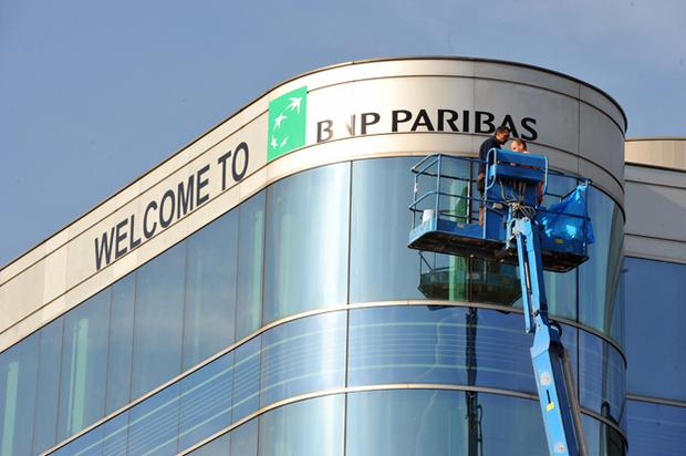 Workers hang the sign 'Welcome to BNP Paribas' on a building in Brussels city center (DOMINIQUE FAGET/AFP/Getty Images)