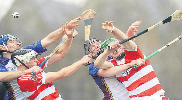 Tony Murphy (left) and Brian Corry, of Cork IT, battle it out with Kieran Joyce and Tom Stapleton (right) during the Fitzgibbon Cup semi-final at Clanna Gael Fontenoy in Sandymount yesterday.