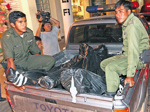 GORY CARGO: Policemen on a truck take the three bodies wrapped in bin-liner bags to the morgue in Santa Cruz, Bolivia, last Thursday morning