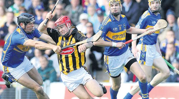 Tommy Walsh tries to get away from Michael Webster at Semple Stadium.