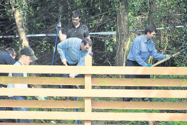 Gardai clearing undergrowth in the grounds of Grange Golf Club in Rathfarnham, Co Dublin, yesterday during their search for the remains of Philip Cairns