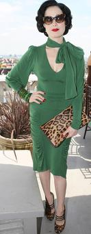 Dita sports the 40's filmstar look in this green dress with pussycat bow, accessorized with leopard print bag and shoes. The outfit is completed with her trademark red lipstick and nailpolish. Photo: Getty Images
