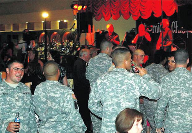 US troops in army fatigues enjoy the festivities at a wedding in Co Clare last week after they were invited to join the party by the groom. Their Iraq-bound aircraft had earlier been grounded at Shannon Airport with technical problems
