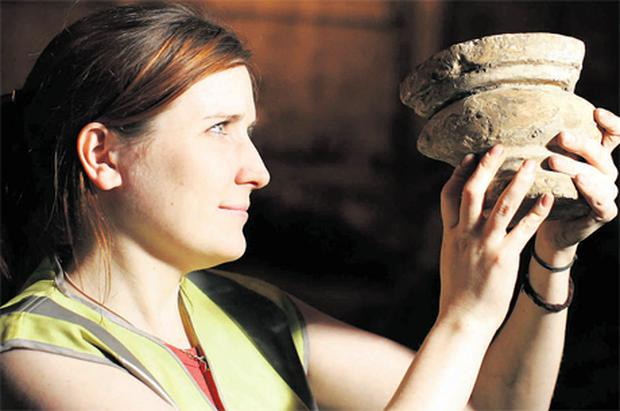 Archaeologist Ciara Burke holds a column found in the foundations of the 17th century Smock Alley Theatre, in Dublin