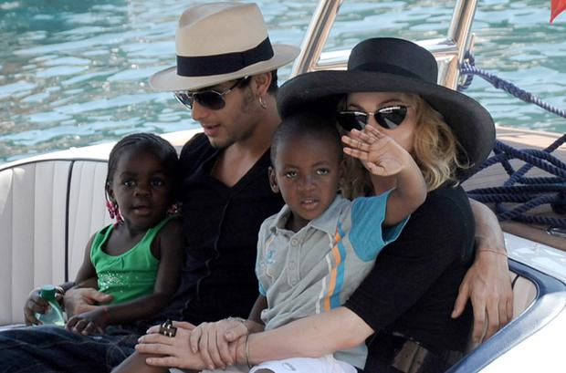 Jesus Luz holding Mercy James and Madonna with son David Banda. Photo: Getty Images