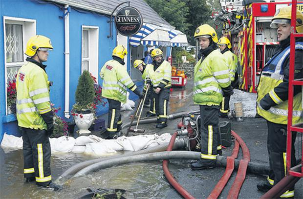 Firemen pumping water from outside a pub in Athea, Co Limerick yesterday.