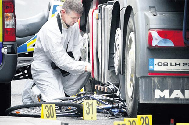 A garda forensic officer examines the scene of the crash between the truck and the cyclist on Wellington Quay, Dublin.