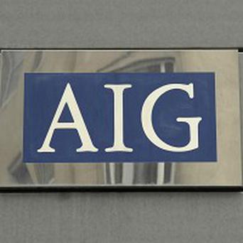 Insurer AIG has slashed top executives' salaries to comply with pay restrictions