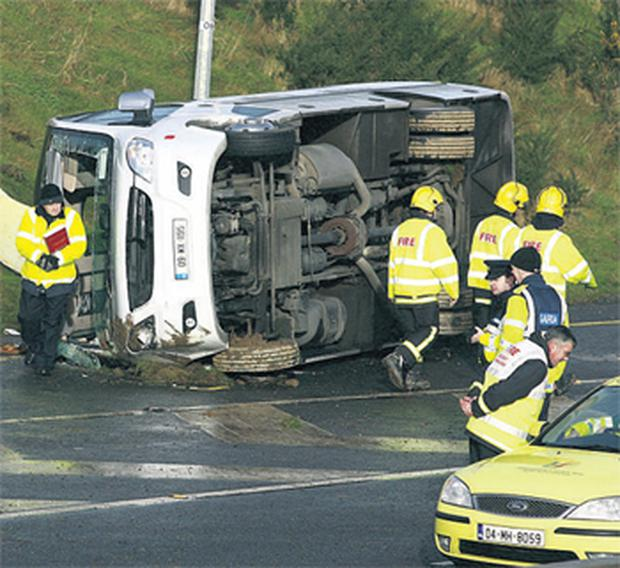 A minibus lies on its side after skidding out of control on icy roads and crashing on the N11 outside Gorey, Co Wexford. One woman died in the incident