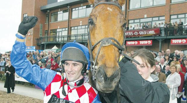Brian Harding raises his arm in the winner's enclosure after riding Ferdy Murphy's Granit D'Estruval to victory in the 2004 Irish Grand National at Fairyhouse