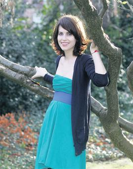 Green bandeau dress, €43, and blue belt, €16, both American Apparel; navy cardigan, €9, Penney's; black tights, €42, by Wolford at Brown.