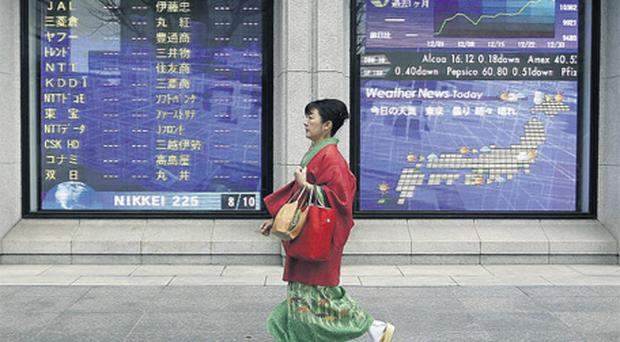 A woman in kimono walks past a stock quotation board outside a brokerage in Tokyo