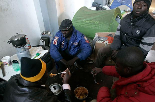 African immigrants cook in a makeshift camp in the countryside near the village of Rosarno, southern Italy. They were forced to leave their homes after racial unrest