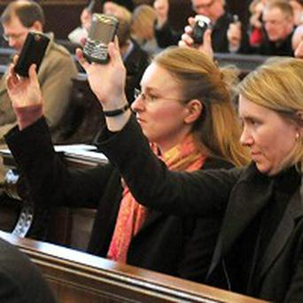 Congregation hold up phones to be blessed at the Corporation of the City of London's church, St Lawrence Jewry