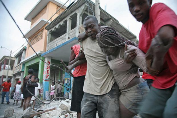 A Haitian woman is helped after being trapped in rubble in Port-au-Prince. Photo: Getty Images
