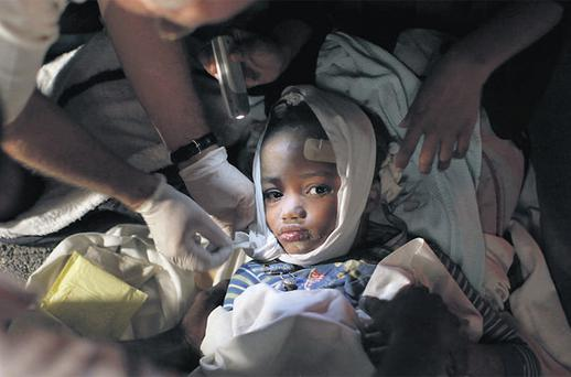 An injured child receiving medical treatment yesterday after the devastating earthquake struck Haiti's capital Port-au-Prince