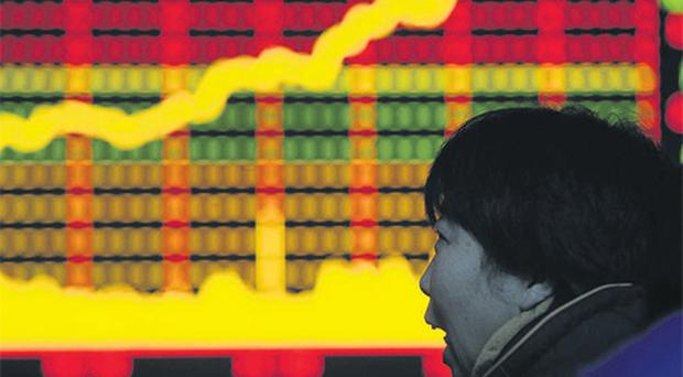 A woman looks at an electronic board with stocks information at a brokerage house in Hefei, Anhui province yesterday