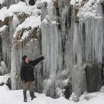 Natural England nature reserve manager Chris McCarty looks at some gigantic icicles at an 'ice cathedral'