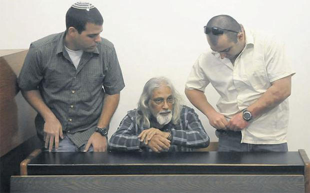Goel Ratzon (centre) appearing in Tel Aviv District Court yesterday. Israeli police have detained Ratzon on suspicion of incest and abuse of women and children they allege he kept like slaves in various homes around Tel Aviv.