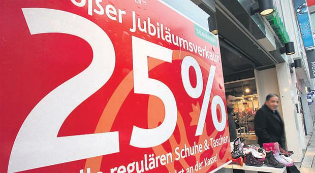A shopper exits a store advertising sales in Frankfurt yesterday. Germany's economy shrank more than economists forecast last year even as government stimulus measures and a rebound in exports pulled it out of a recession in the second quarter.