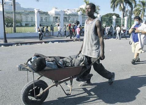 A man transports an earthquake victim in a wheelbarrow in front of the destroyed presidential palace in Port-au-Prince yesterday