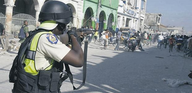 A Haitian policeman levelling his rifle at a crowd during looting in Port-au-Prince yesterday