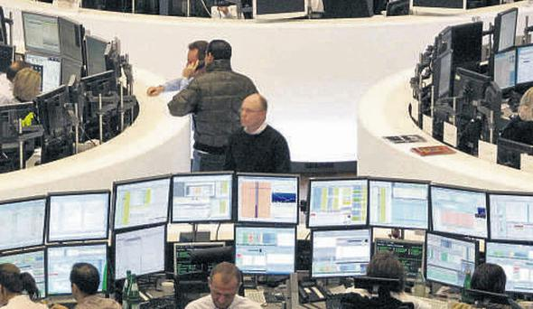 Traders at their desks at the Frankfurt stock exchange yesterday