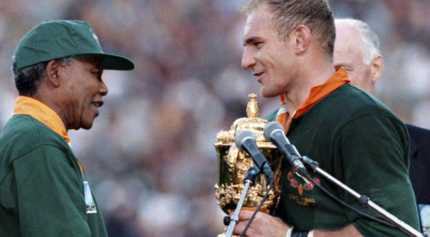 Nelson Mandela, then president of South Africa, presents the Rugby World Cup trophy to Springboks captain Francois Pienaar, after South Africa beat New Zealand in the 1995 final. Photo: Getty Images
