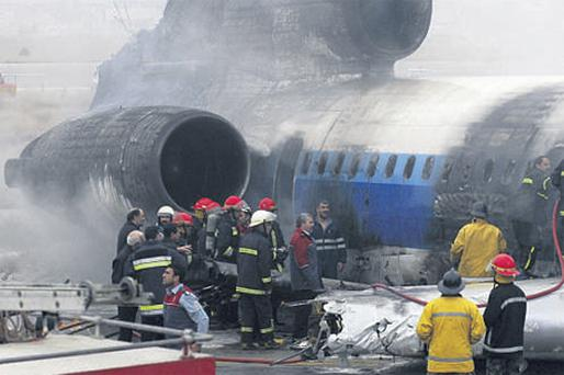 Emergency services put out the fire after the Russian-made Tupolev crash-landed and burst into flames at Mashhad city airport