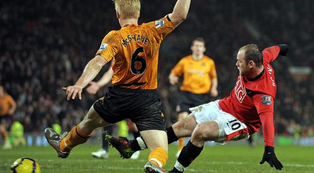 Wayne Rooney slots home his fourth goal against Hull City despite Paul McShane's desperate efforts to block the shot Photo: Getty Images