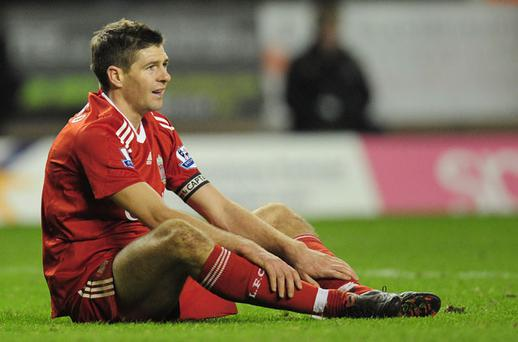 A dejected Steven Gerrard sits on the Molineux turf after his team's scoreless draw against Wolves last night Photo: Getty Images