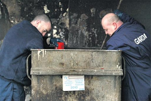 Gardai search bins outside semi-derelict flats near the scene of the €1m violent robbery of a diamond dealer at the Travelodge hotel in Ballymun town centre yesterday