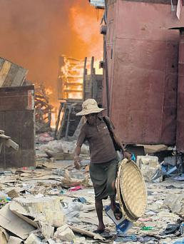 DEVASTATION: A woman walks near a fire engulfing stores in a market area in Port-au-Prince. Photo: Marco Dormino