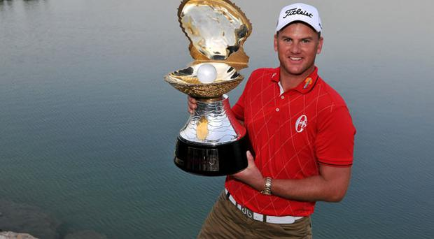 Robert Karlsson of Sweden poses with the trophy after winning the Qatar Masters in Doha yesterday Photo: Getty Images