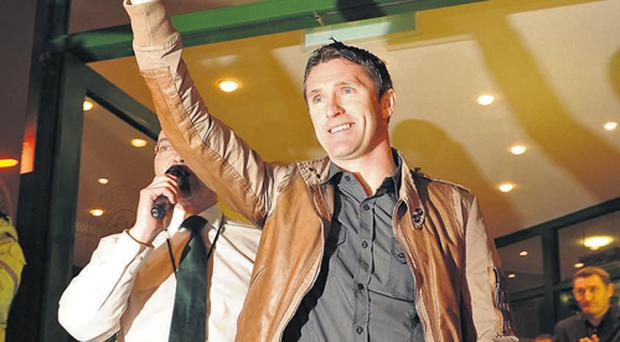 Under the watchful eye of his new manager Tony Mowbray, new Celtic signing Robbie Keane waves to the thousands of supporters who had gathered to welcome him to Celtic Park last night