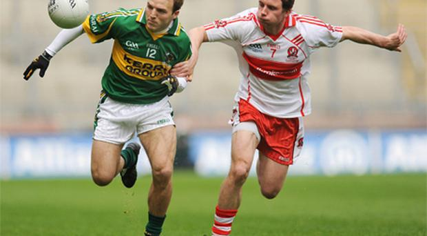 Kerry's Darran O'Sullivan in action against Derry's Sean Leo McGoldrick in last year's Division 1 final before hoisting the trophy after last year's victory