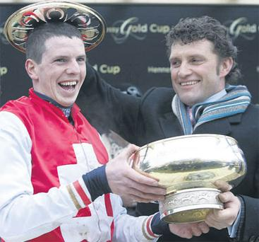 If the cap fits . . . . winning jockey Alain 'Squeaky' Cawley shares a joke with trainer Paul Nolan after receiving the Hennessy Gold Cup for Joncol's success in the Leopardstown feature yesterday NIALL CARSON/PA